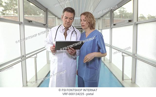 Medium lockdown shot of a hospital corridor where a doctor and a nurse are talking