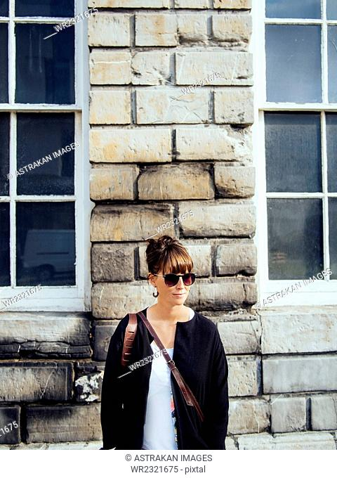 Fashionable woman standing against wall outdoors