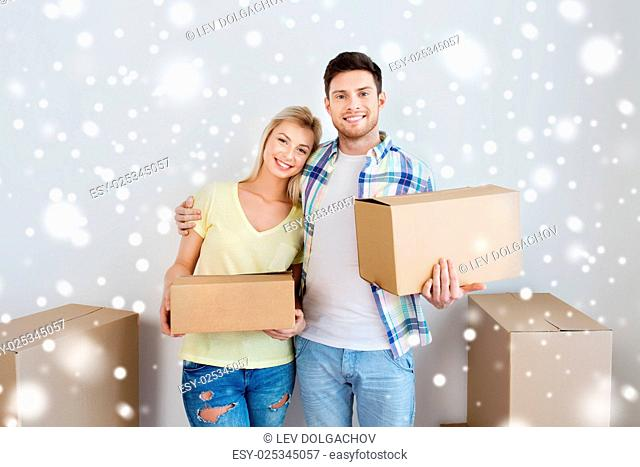 home, people, repair and real estate concept - smiling couple with big cardboard boxes moving to new place over snow