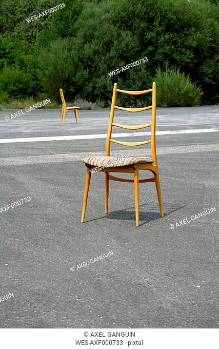 Two wood chairs on a runway