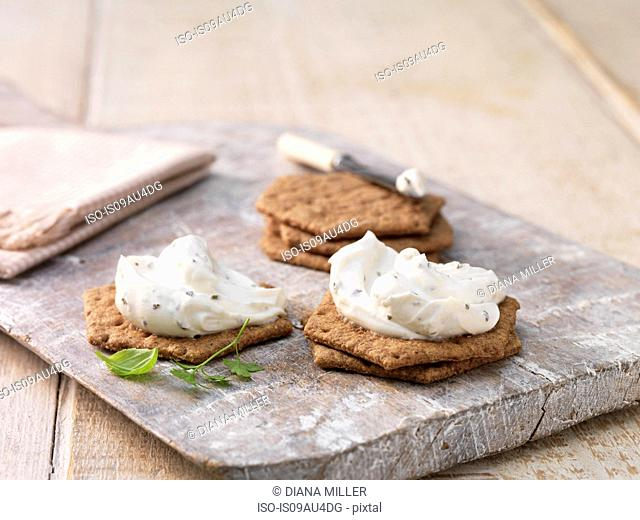 Garlic and herb soft cheese on hexagon crackers on whitewashed cutting board