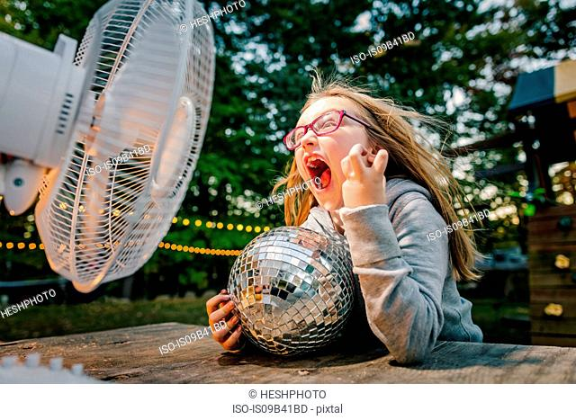 Girl screaming in front of windy electric fan at garden table
