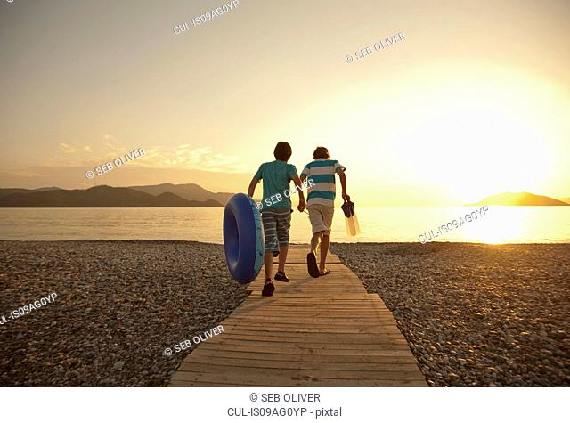 Teenage boy and brother running toward sea, Fethiye, Turkey