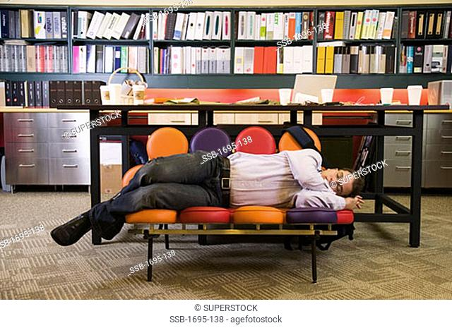 Front view of a businessman sleeping on a couch