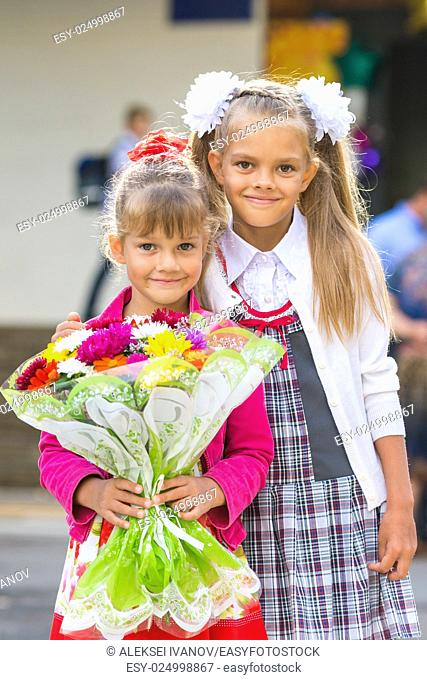 Portrait of two girls in school September 1 - the first-grader and her younger sister with a bouquet in hands