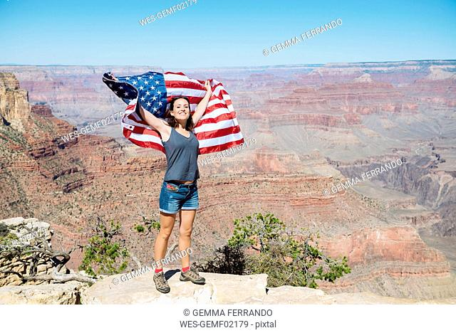 USA, Arizona, smiling woman with American flag at Grand Canyon National Park