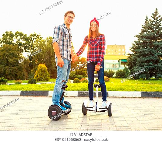 Young couple riding hoverboard - electrical scooter, personal eco transport, gyro scooter, smart balance wheel. New modern technologies