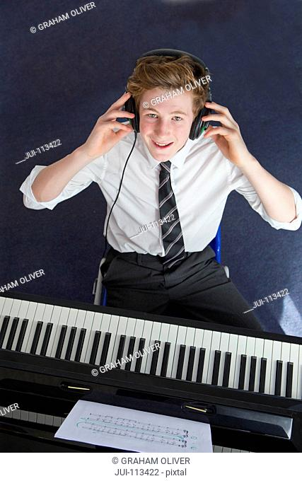 Portrait smiling high school student with headphones playing piano in music class
