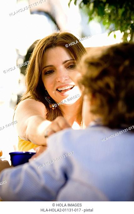 Mid adult woman feeding her son in a restaurant