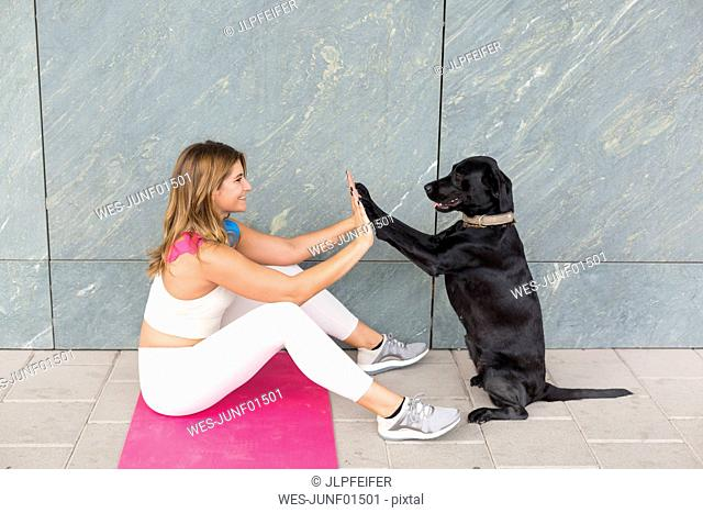 Young woman sitting on Yoga mat doing relaxation exercise with her black dog
