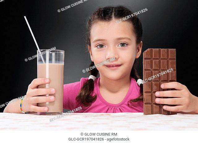 Girl holding a bar of chocolate and a glass of chocolate milkshake