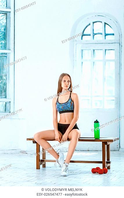 Muscular young woman athlete resting with water on white background
