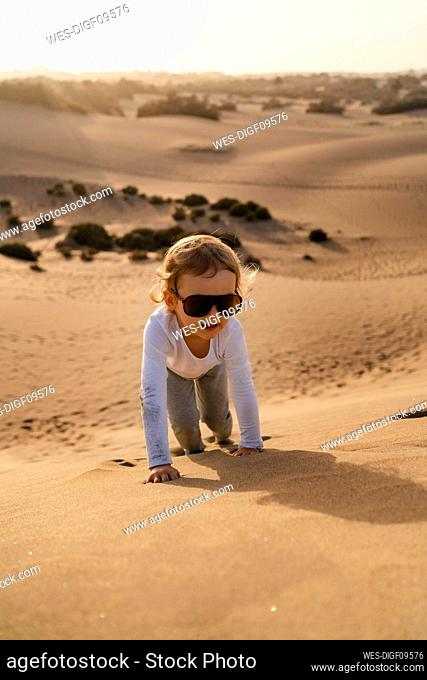 Girl crawling up sand dune, Gran Canaria, Spain