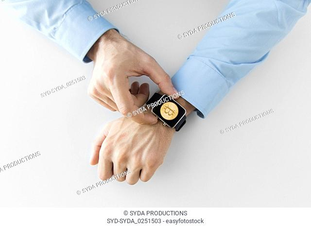 close up of hands with bitcoin on smart watch