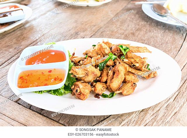 Deep fried chicken wings with salt and herbs in dish on wooden background