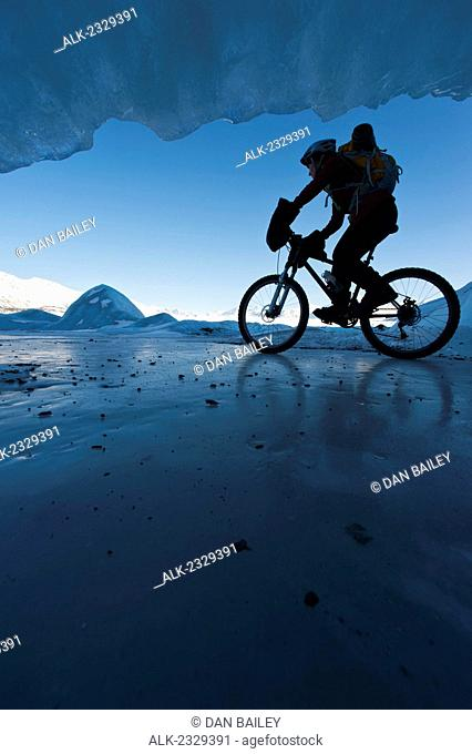 Woman Mountain Biking On The Ice Of The Knik Glacier In Front Of An Ice Cave, Chugach Mountains, Southcentral Alaska, Winter