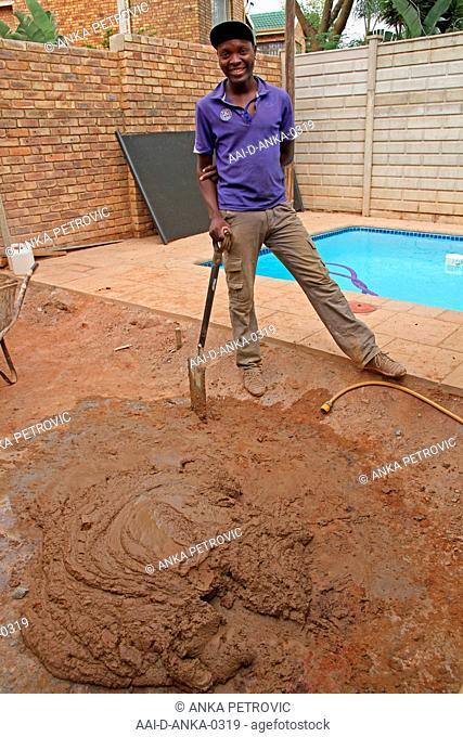 Worker shoveling cement concrete mixture near swimming pool, construction site, Moreleta Park, Pretoria, Gauteng Province, South Africa