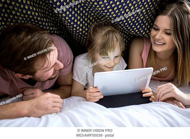 Parents watching something on digital tablet with their daughter under blanket in bed