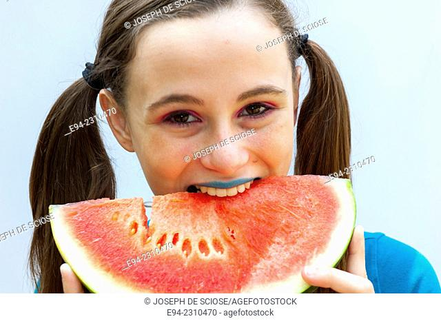 An 18 year old woman eating watermellon and looking at the camera