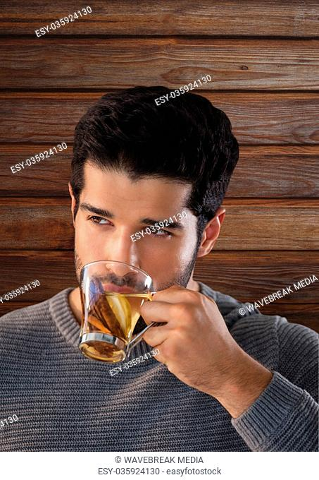 Man against wood with cup of golden liquid