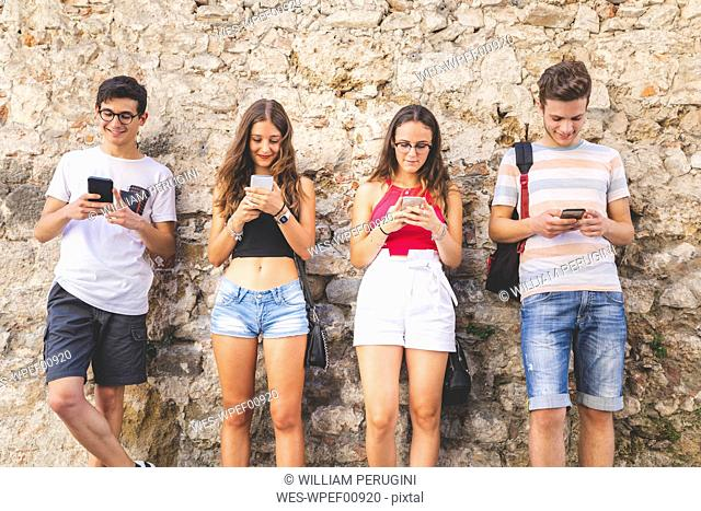 Group of friends standing at a wall using their cell phones