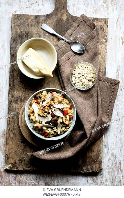Bowl of porridge with bell pepper, champignon and parmesan