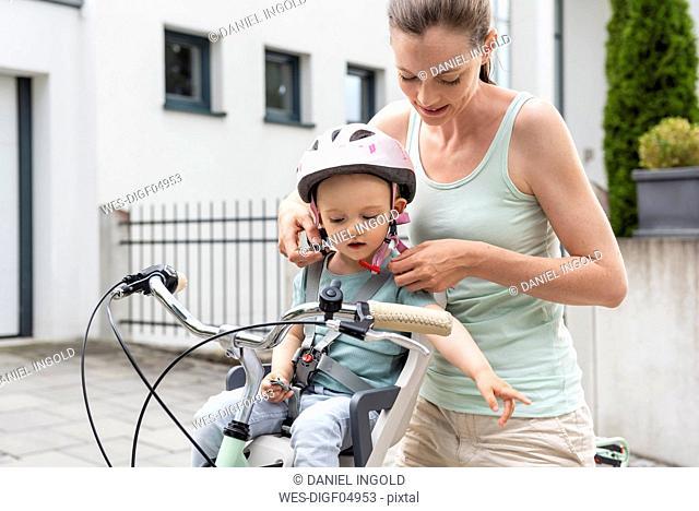 Mother and daughter, daughter wearing helmet sitting in children's seat