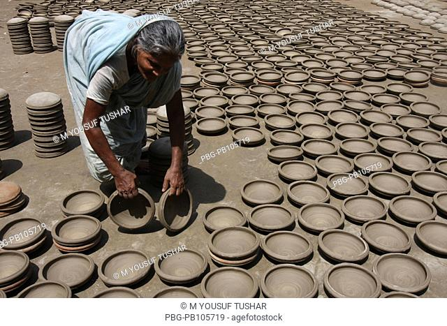 A woman drying clay pots on the sun before burning at fire Manikganj, Bangladesh September 2009