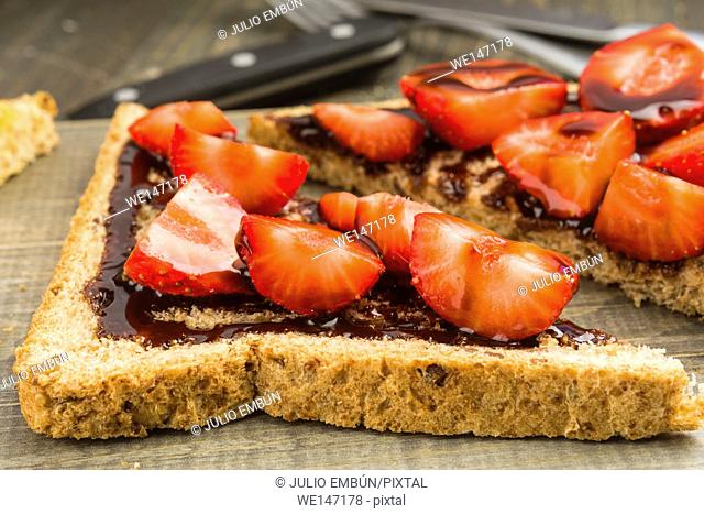 triangles of bread with chocolate and chopped strawberries on wood on wooden