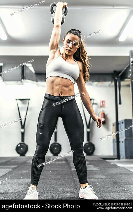 woman with dumbbells in the gym doing crossfit
