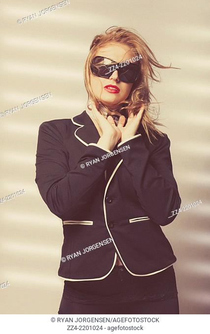Beautiful young woman with exquisite make-up and hairstyle posing in studio wearing high quality fashion. Prestige style