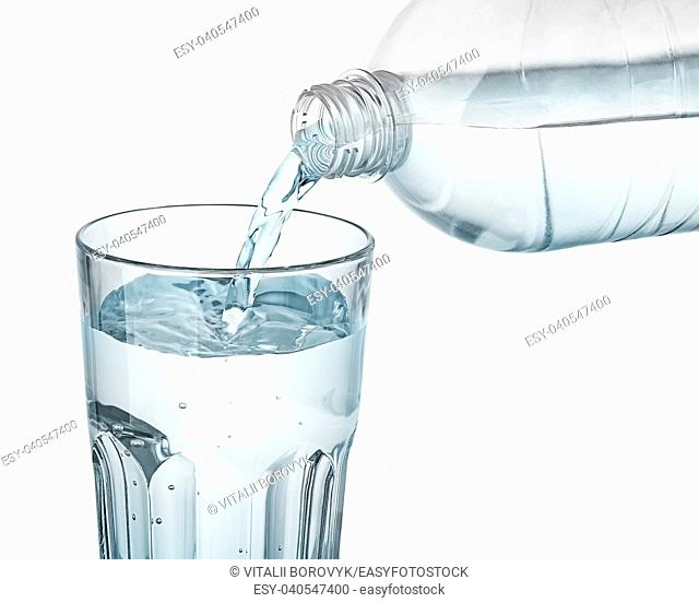 Water is poured into a glass. Plastic bottle. Isolated on white background