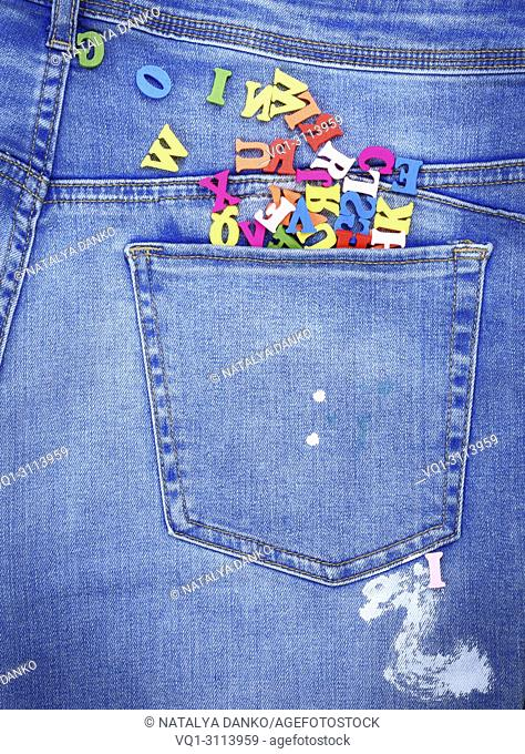 multicolored wooden letters of the English alphabet pour out from the back pocket of the jeans, close up