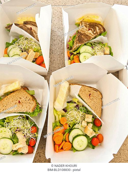 Sliced vegetables and sandwiches in lunch boxes
