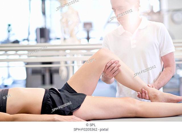 Physiotherapist manipulating woman's leg