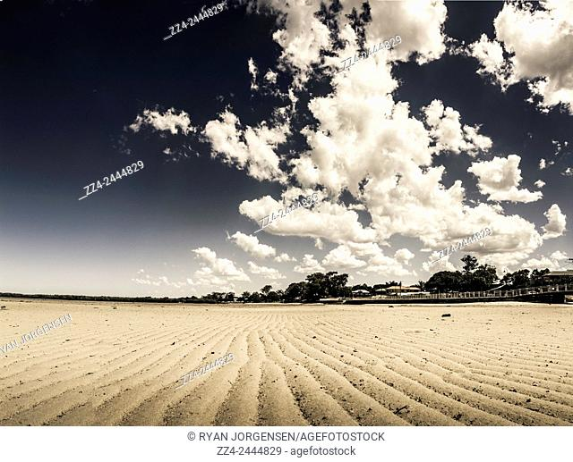 Desert like landscape scene of a low tide beach with waves of sand leading to a dramatic cloudscape. 3 photo stitch: taken Deception Bay, Queensland, Australia