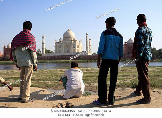 Local villagers viewing at Taj Mahal Seventh Wonders of World on south bank of Yamuna river , Agra , Uttar Pradesh , India UNESCO World Heritage Site