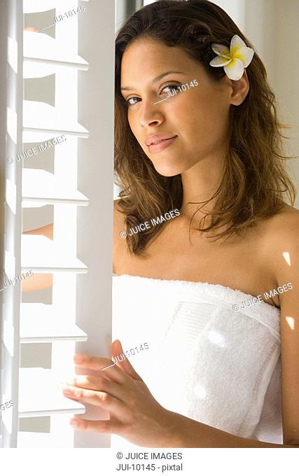 Young woman in bath towel by shutters, flower in hair, portrait
