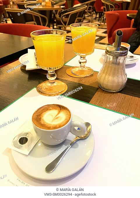 Cup of coffee and two glasses of orange juice in a cafe