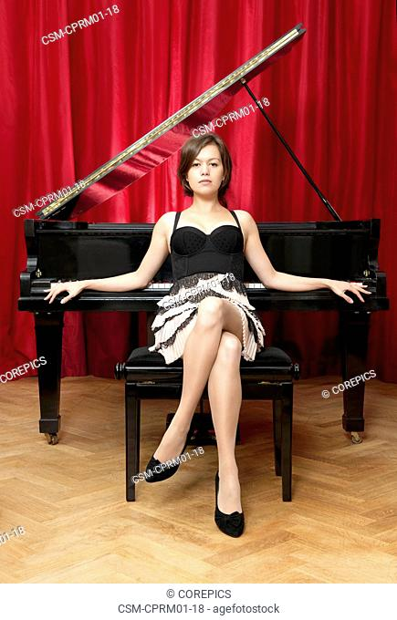 Portrait of a female musician, sitting haughtily in front of a grand piano