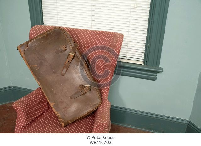Old suitcase on a chair