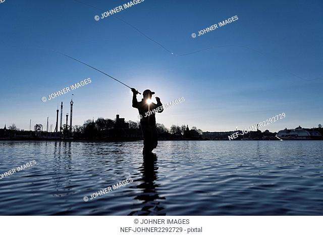 Silhouette of man fishing