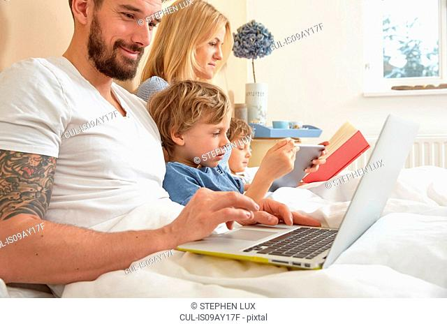 Mother and father in bed with sons using technology, reading book