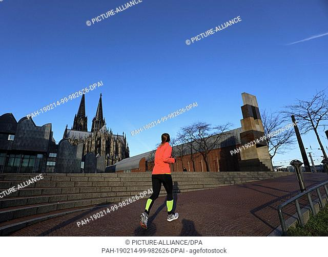 14 February 2019, North Rhine-Westphalia, Köln: A jogger walks past the cathedral in the morning sun. Photo: Oliver Berg/dpa