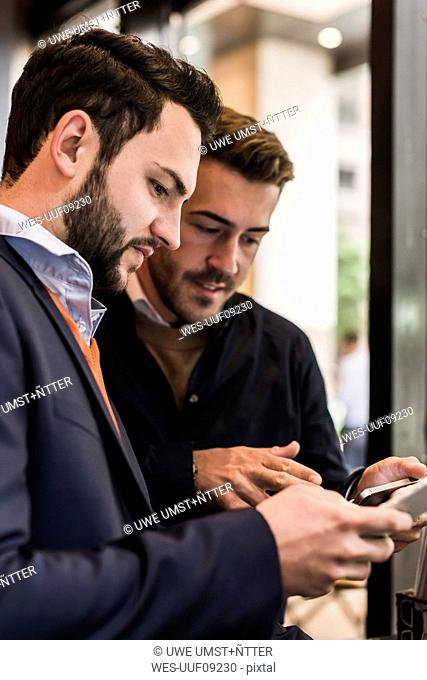 USA, New York City, Businessmen checking mobile devices