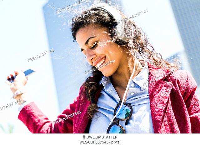 Happy young woman with headphones outdoors
