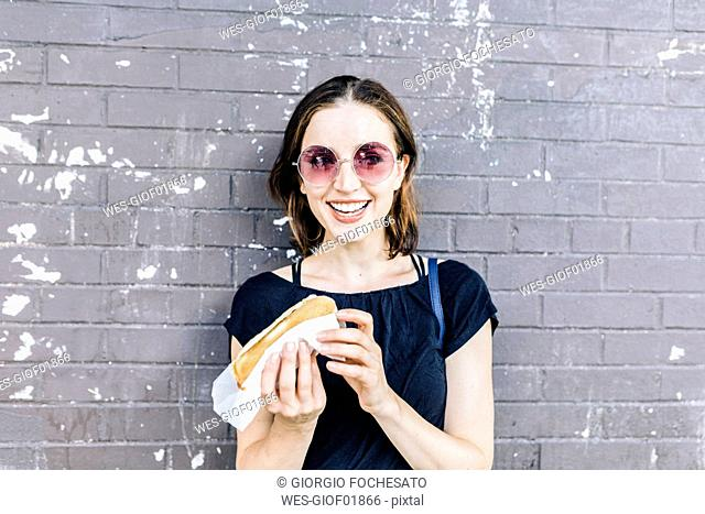 Portrait of smiling woman with Hot Dog in front of wall