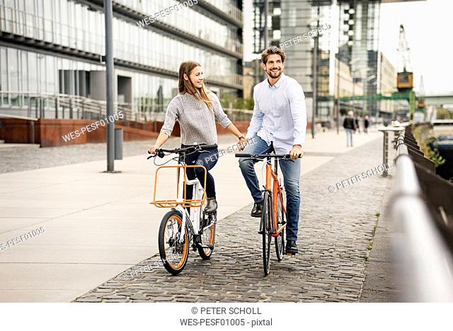 Smiling couple riding bicycle in the city