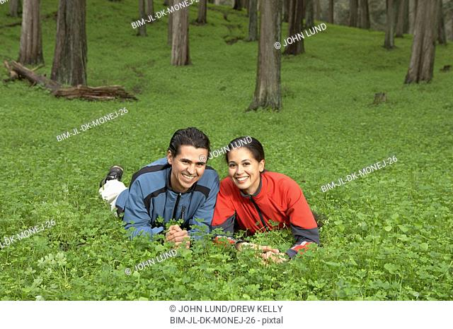 Portrait of couple laying in meadow