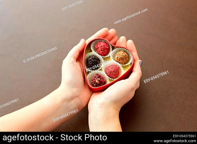 hands with candies in heart shaped chocolate box